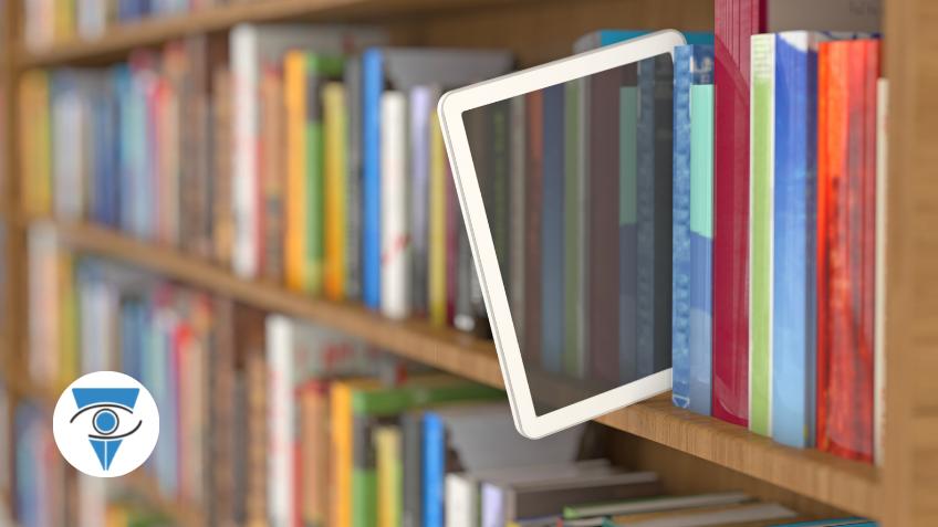 Foto de una tablet asomada en una biblioteca llena de libros.